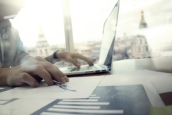 business documents on office table with laptop computer and graph financial diagram and man working in the background